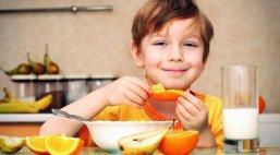 niño desayunando con leche y fruta